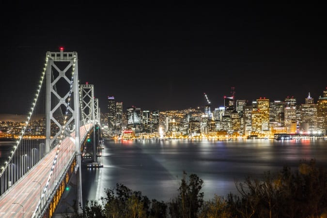 A long-exposure shot of a bridge with red light trails on it and San Francisco skyline on the other side